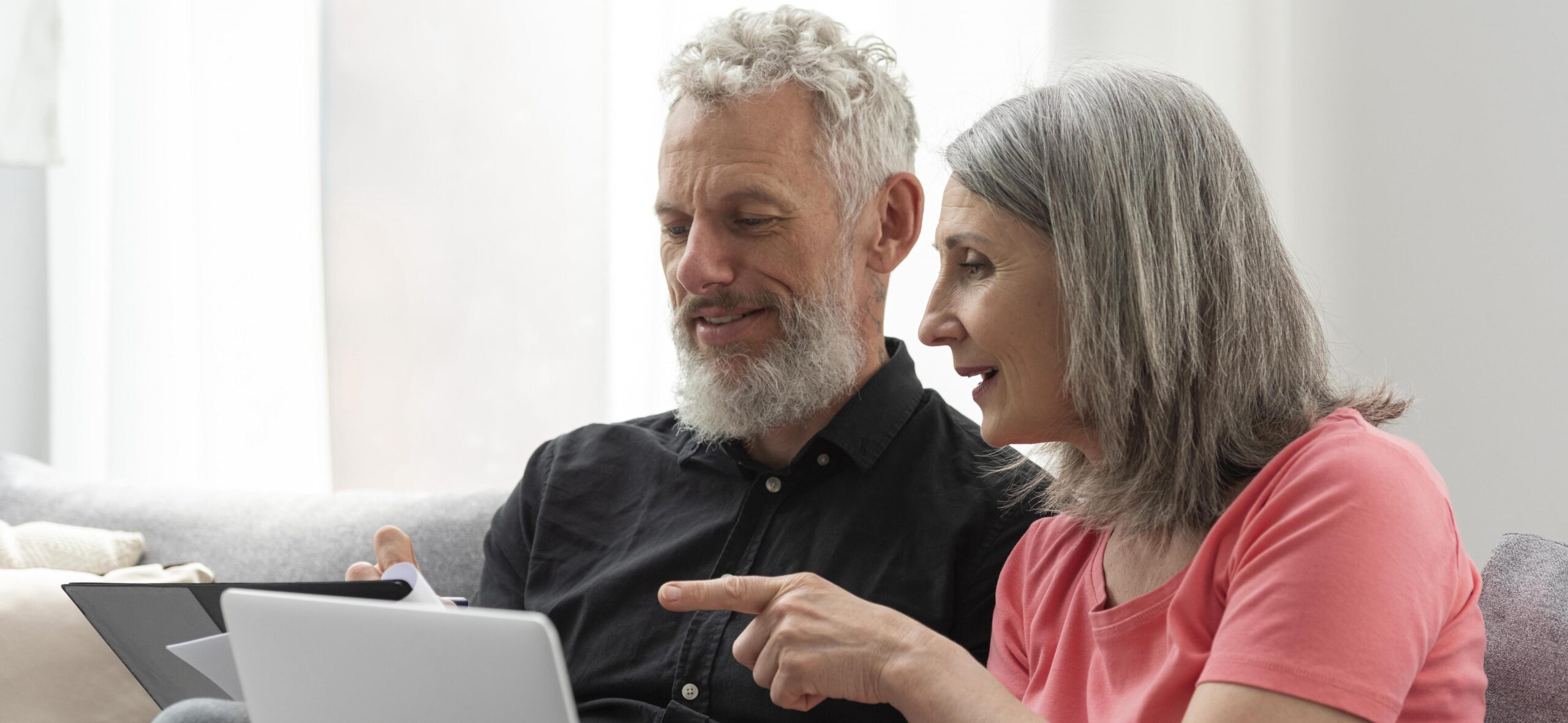 older-couple-at-home-on-the-couch-using-laptop
